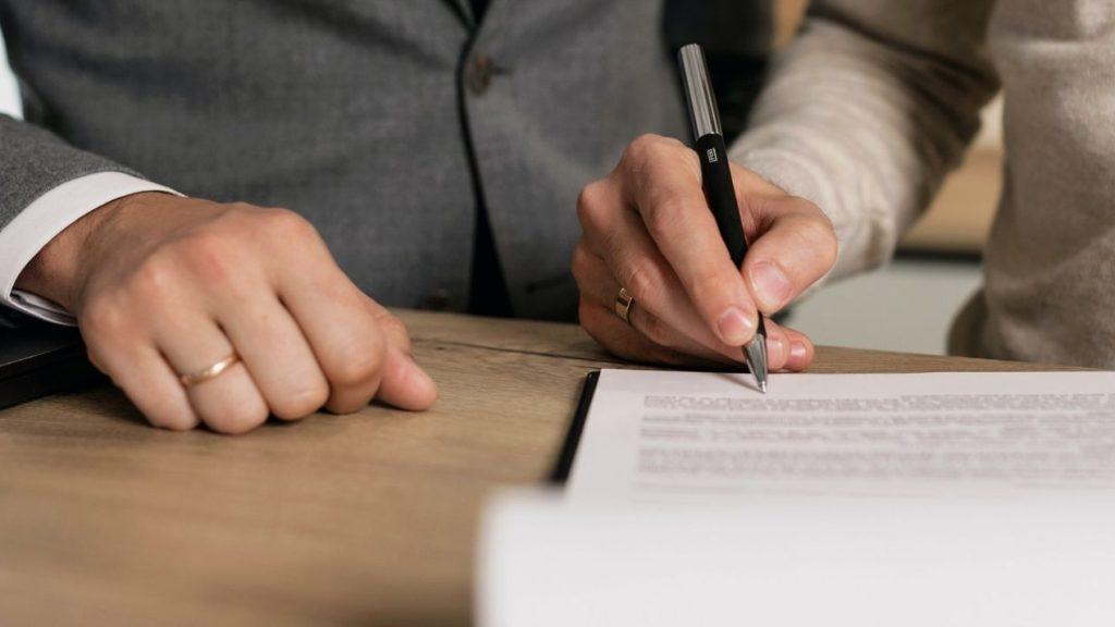 2 personnes signant des documents